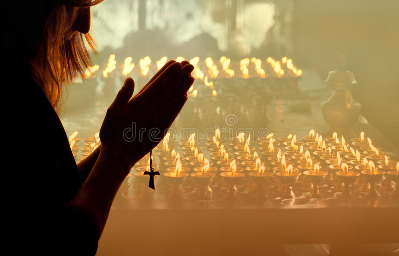 Woman Praying. With candles and smoke from incense