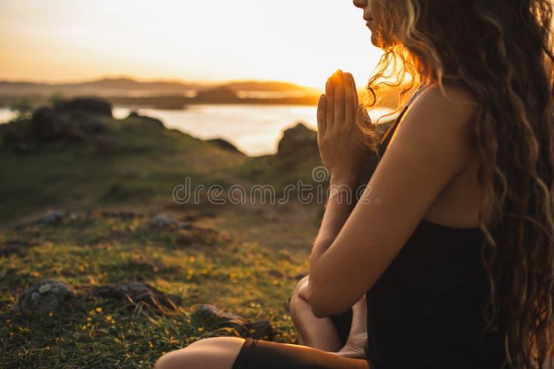 Woman praying alone at sunrise. Spiritual and emotional concept. Woman praying alone at sunrise. Nature background. Spiritual and emotional concept. Sensitivity stock photography