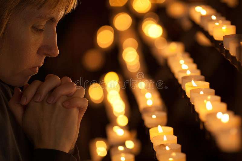 Woman praying in church stock images