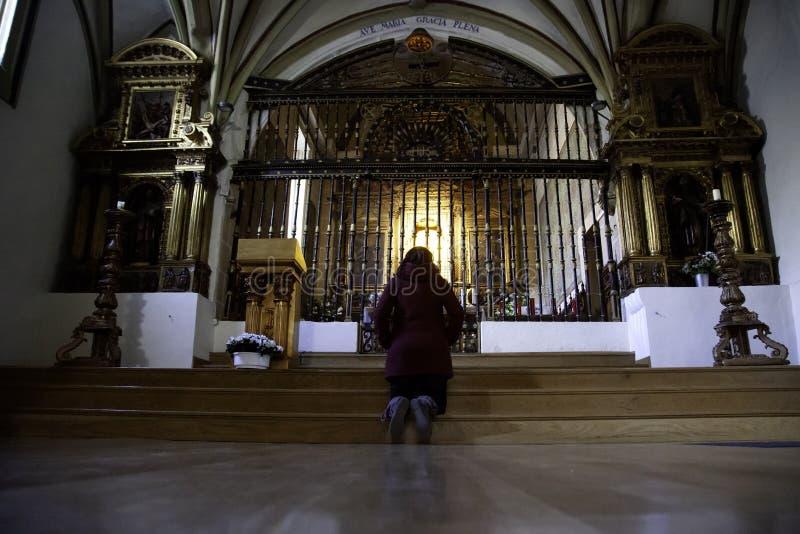 Woman praying in church royalty free stock photo