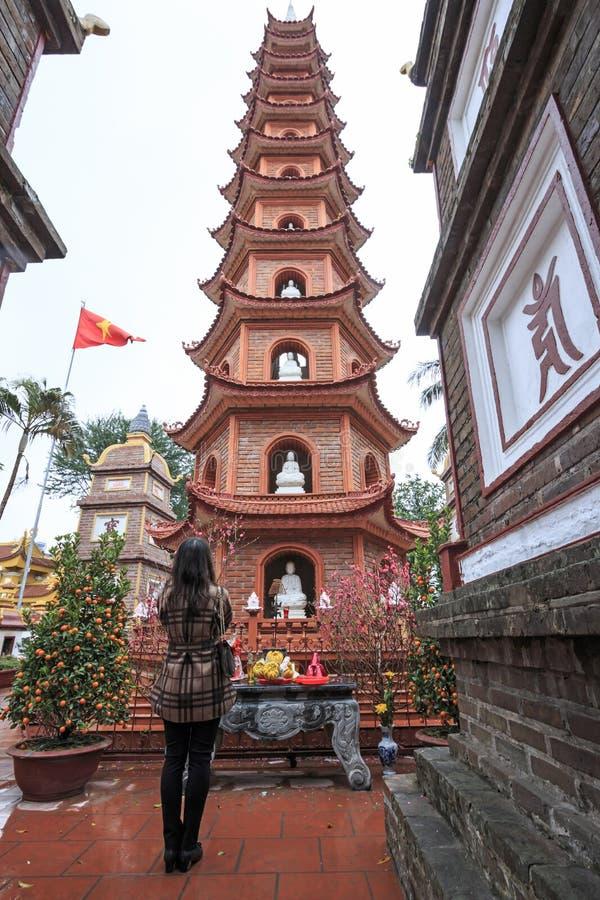 Woman praying in fron of the Tran Quoc Pagoda in Hanoi, Vietnam. Hanoi, Vietnam - February 23, 2016: Woman praying in fron of the Tran Quoc Pagoda in Hanoi royalty free stock photo