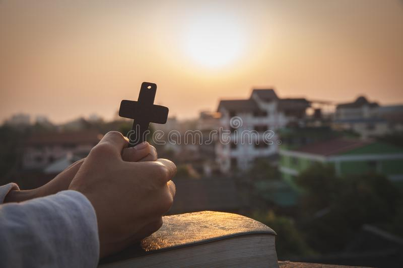 Woman praying while holding Bible and cross, Pray in the Morning , Woman praying with hands together on the Sunrise background stock images
