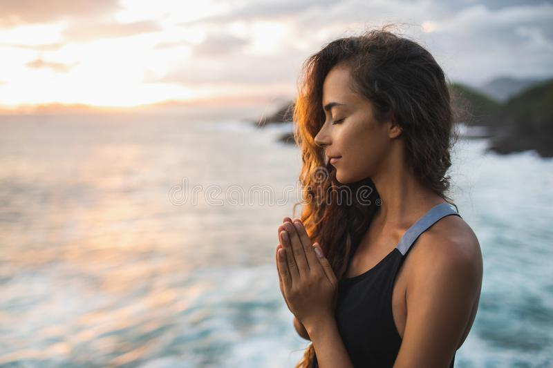 Woman praying and meditating at sunset with beautiful ocean and mountain view. Young woman praying and meditating alone at sunset with beautiful ocean and stock images