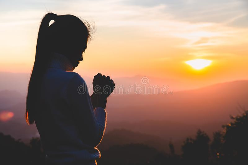 Woman praying in the morning on the sunrise background. Christianity concept. Pray background. Faith hope love concept royalty free stock image