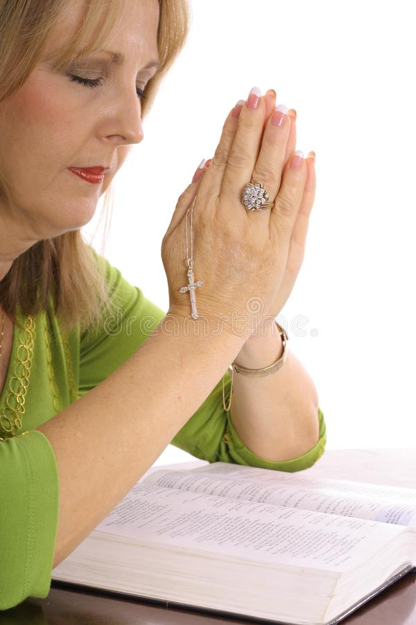 Woman praying over the bible with rhinestone cross stock photo