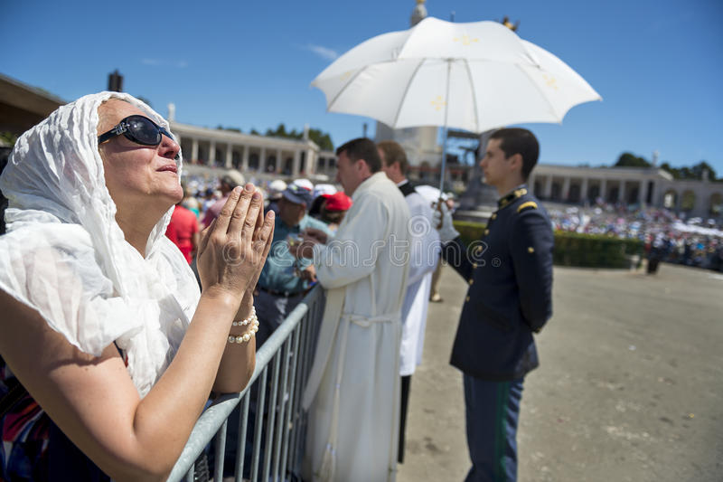 Woman praying at the Sanctuary of Fatima during the celebrations of the apparition of the Virgin Mary in Fatima, Portugal. Fatima, Portugal - May 13, 2014 stock photos