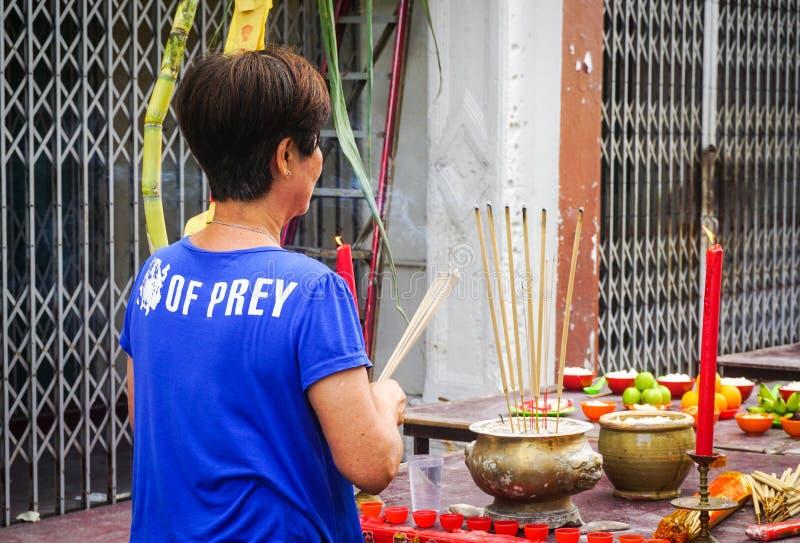 A woman praying on street at Chinatown in Melaka, Malaysia stock photo