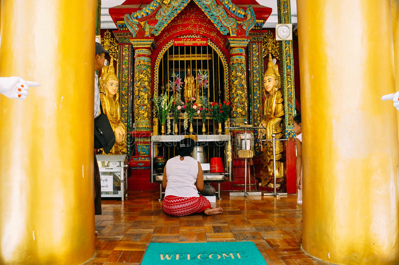 A woman praying in a temple at Shwedagon Pagoda in Yangon. stock images