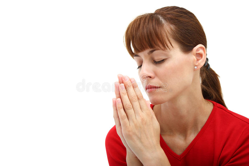 A woman praying to God. Close-up of a woman praying to God with closed eyes isolated on a white background stock image