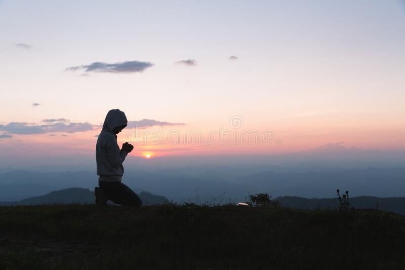 A women is praying to God on the mountain. Praying hands with faith in religion and belief in God on blessing background. Power of. A woman is praying to God on stock photos