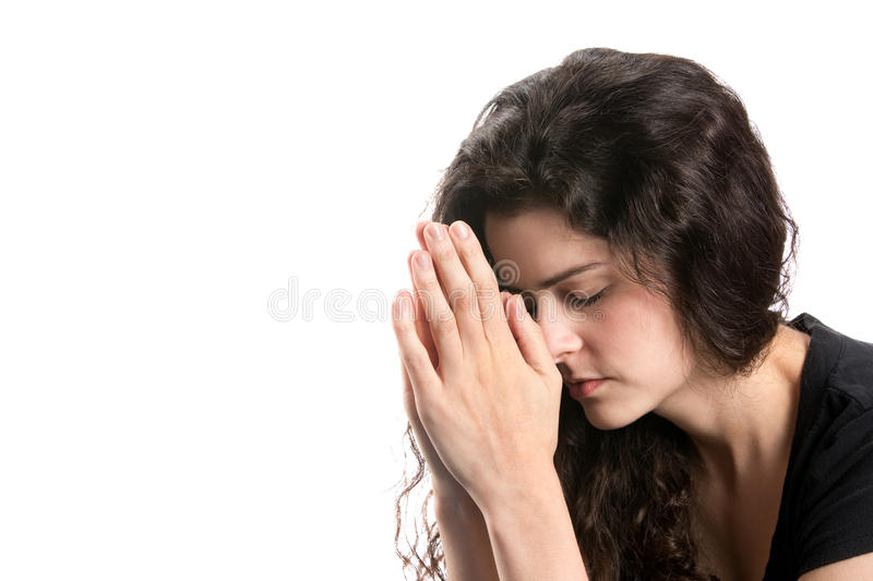 Woman Praying. Young woman prays with head bowed and hands together royalty free stock photos