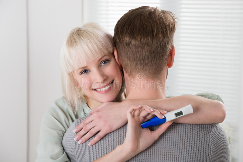 Woman With Pregnancy Test Hugging Man royalty free stock photos