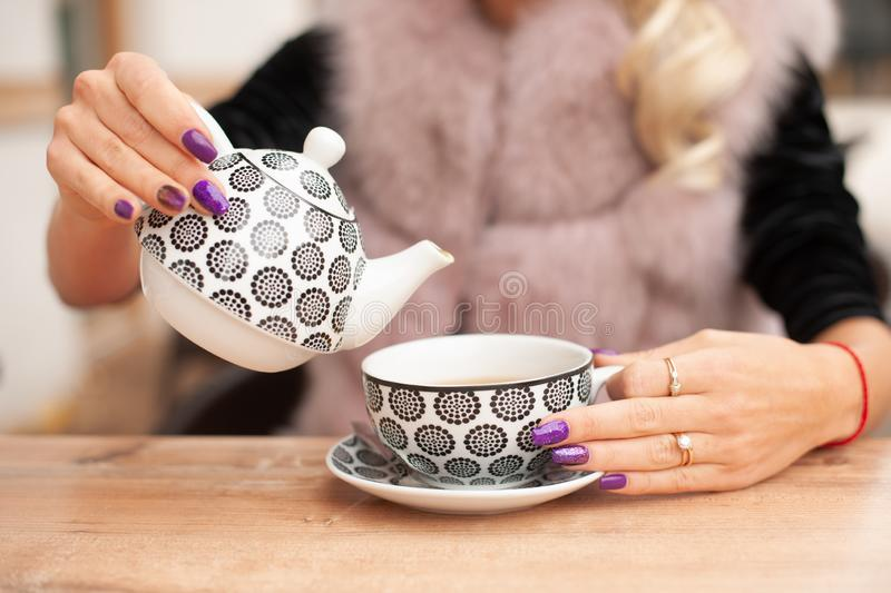 Woman prepare tea on bar terace hold teapot in her hands in ear royalty free stock images