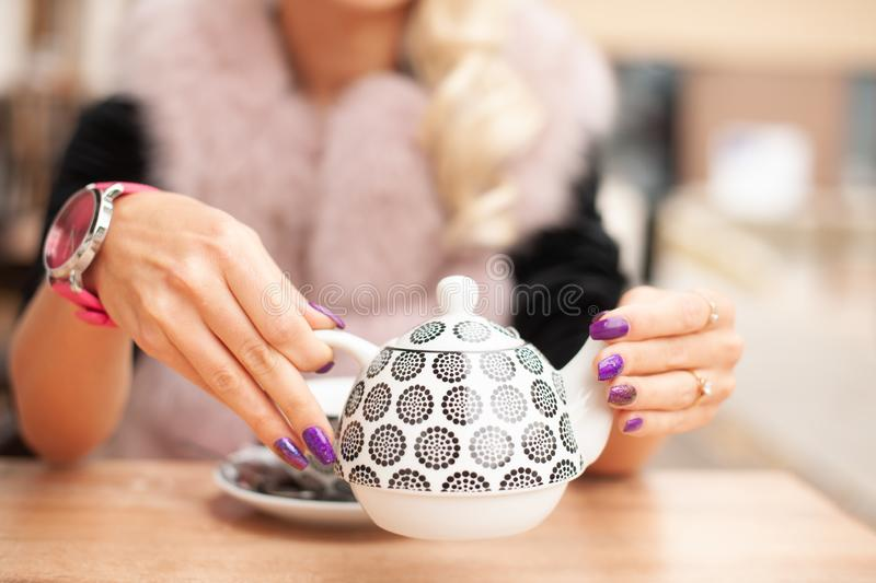 Woman prepare tea on bar terace hold teapot in her hands in early autumn royalty free stock images