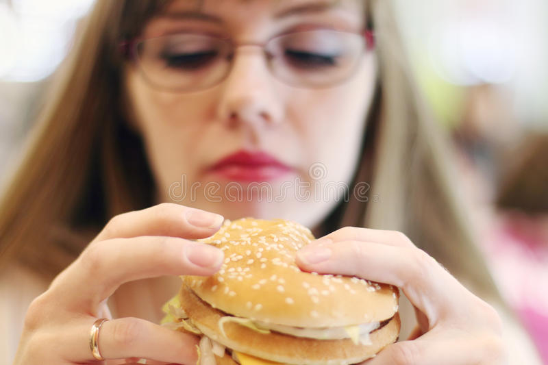 Woman prepares for eating hamburger in cafe, focus on hamburger. Shallow dof royalty free stock images
