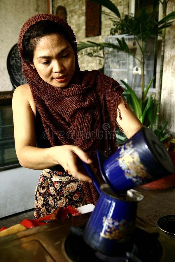 A woman prepares hot cocoa drink manually from freshly ground cocoa beans. CEBU CITY, PHILIPPINES - JUNE 13, 2013: A woman prepares hot cocoa drink manually royalty free stock photography