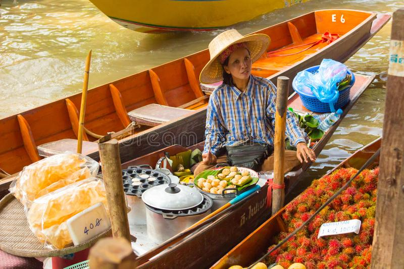 Woman prepares and sells small cakes to damnoen floating market stock image