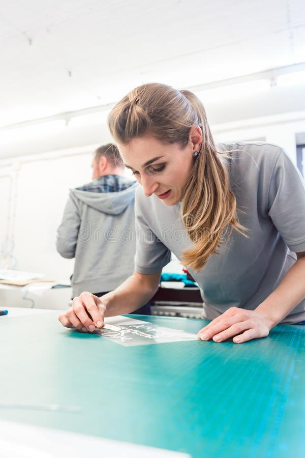 Woman preparing sticker with text to be printed on a T-Shirt. Woman preparing advertisement sticker with text to be printed on a T-Shirt royalty free stock image