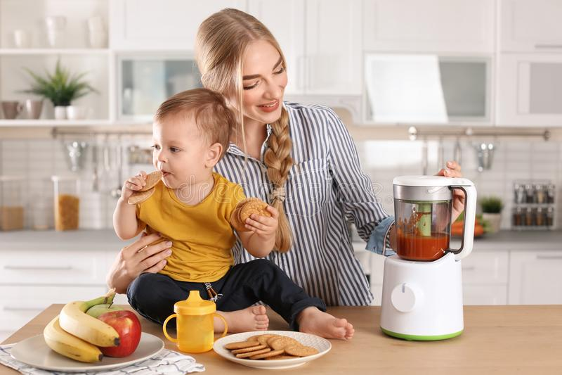 Woman preparing breakfast for her child in kitchen stock images