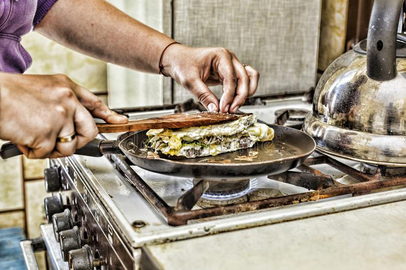 A woman is preparing breakfast at home in the kitchen. Toasts in a frying pan with egg green and bacon. Healthy food. stock photography