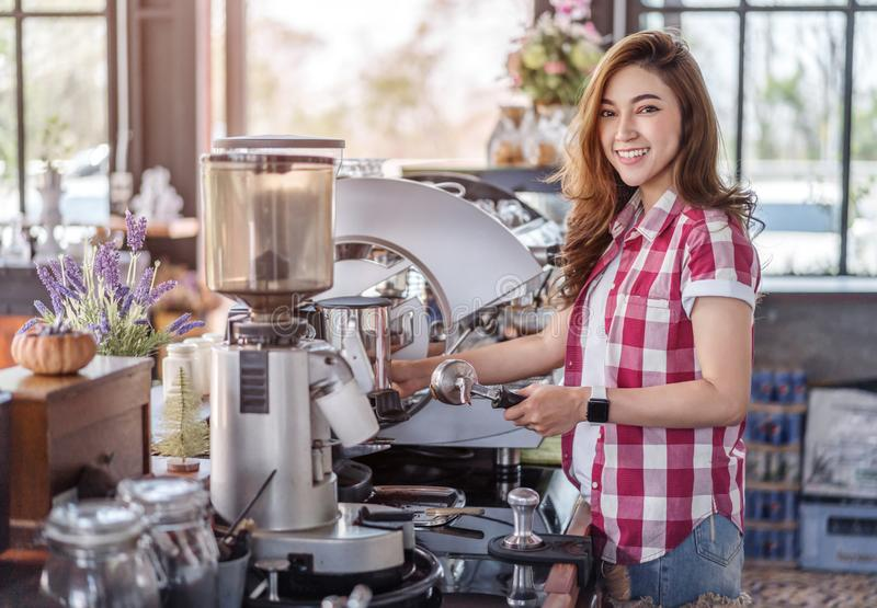 Woman preparing coffee with machine in cafe. Woman preparing coffee with machine in a cafe royalty free stock photography
