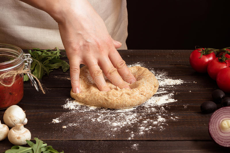 Woman preparing dough for pizza. Hands kneading dough on the wooden table.  royalty free stock photography