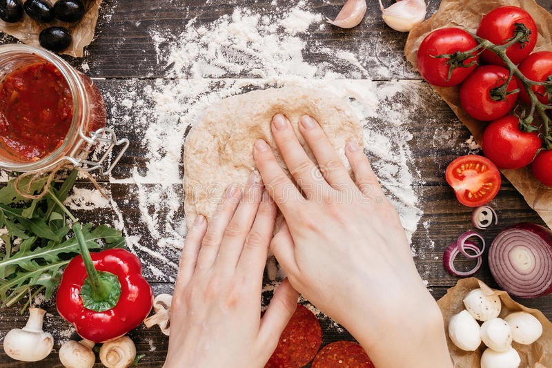 Woman preparing dough for pizza. Hands kneading dough on the wooden table, top view.  royalty free stock photos