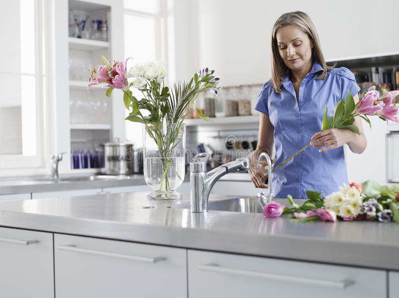 Woman Preparing Flowers For Vase At Kitchen Sink stock images