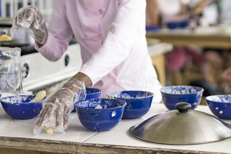 Woman preparing food at an outdoor restaurant. Sprinkling seasoning into one of a group of blue bowls on a table in a close up view of her hands royalty free stock images