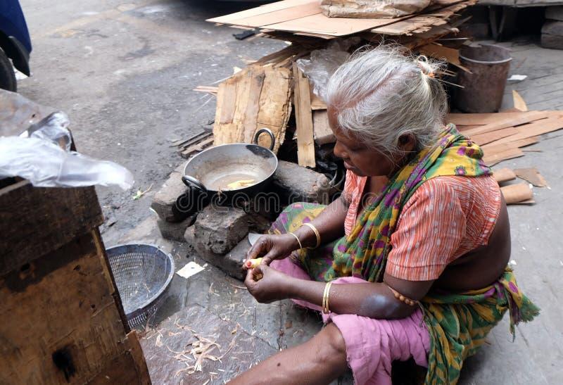 Woman preparing food on street, Kolkata stock photography