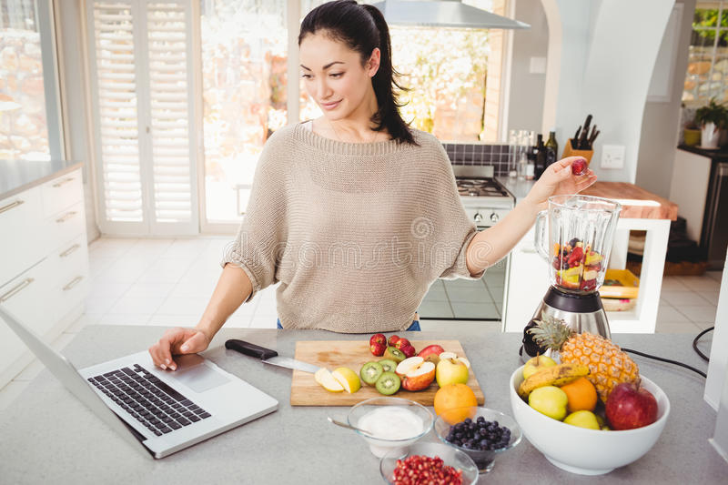Woman preparing fruit juice while working on laptop. At table stock photo