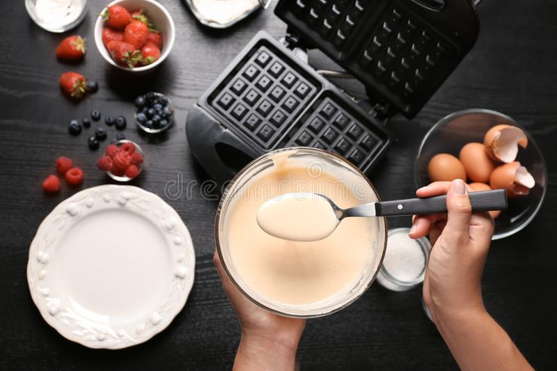 Woman preparing homemade waffles in kitchen, top view stock photography