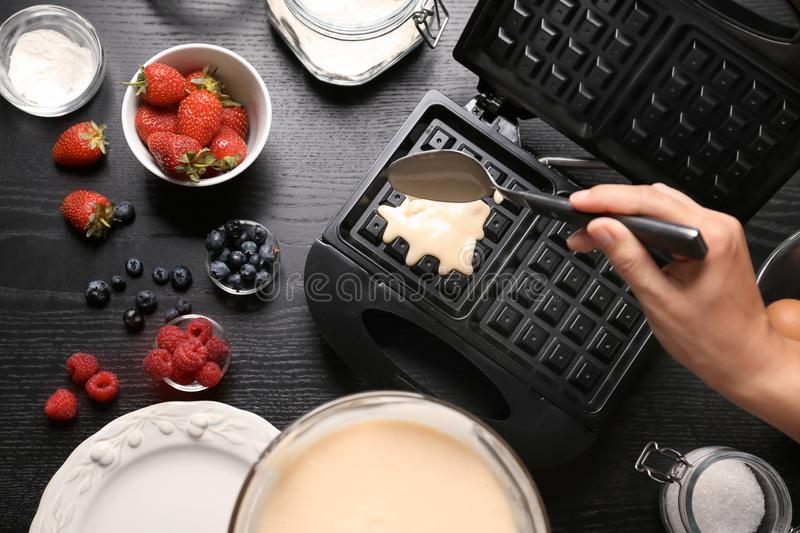 Woman preparing homemade waffles in kitchen, top view stock image