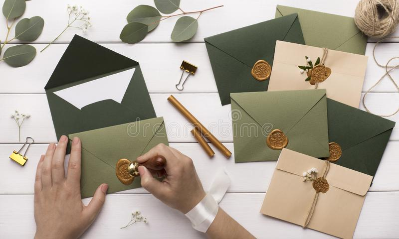 Woman preparing invitations for wedding on white wooden table. Panorama royalty free stock photography