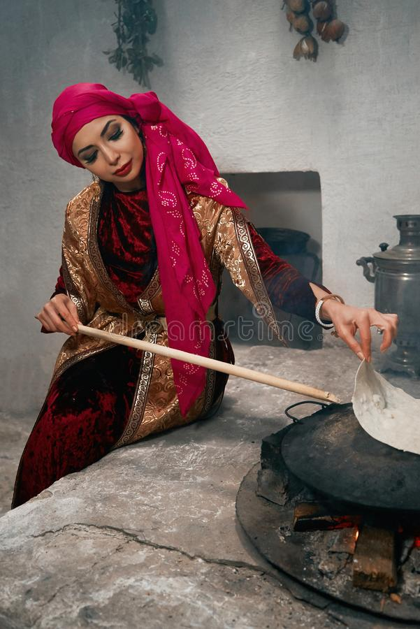 Woman preparing or making borek or bread dough on fire. Cooking traditional Turkish borek, pide, pita or yufka bread. Traditional Turkish food. Woman preparing stock photography