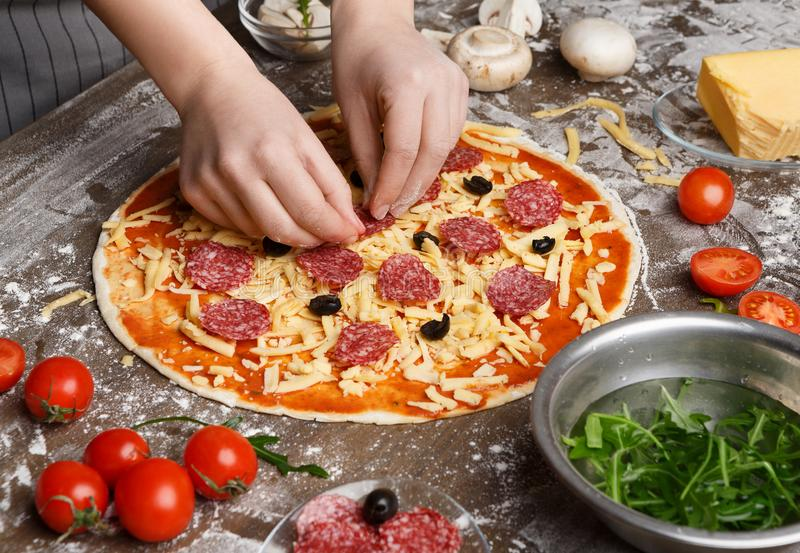 Woman Preparing Pizza, Adding Salami And Black Olives. Closeup stock photos