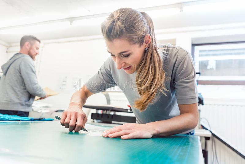 Woman preparing sticker with text to be printed on a T-Shirt. Woman preparing advertisement sticker with text to be printed on a T-Shirt royalty free stock images