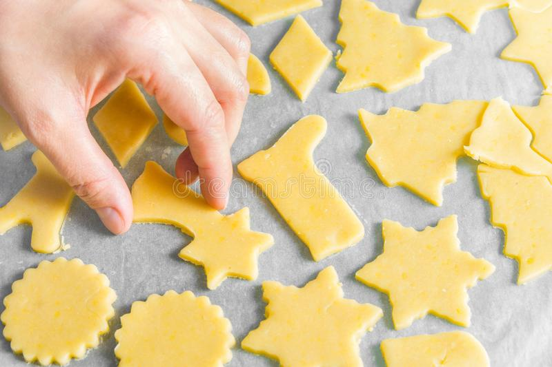Woman preparing to bake homemade unbaked Christmas shortbread cookies in various shapes on tray. Appetizing golden color stock photo