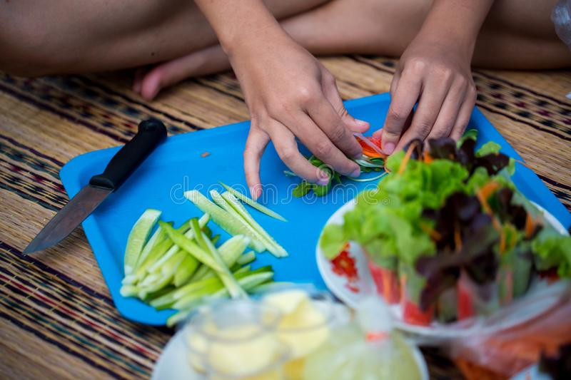 A woman preparing to cook salad on chopping board. fresh vegetables on blue chopping board to cooking salad. royalty free stock photo