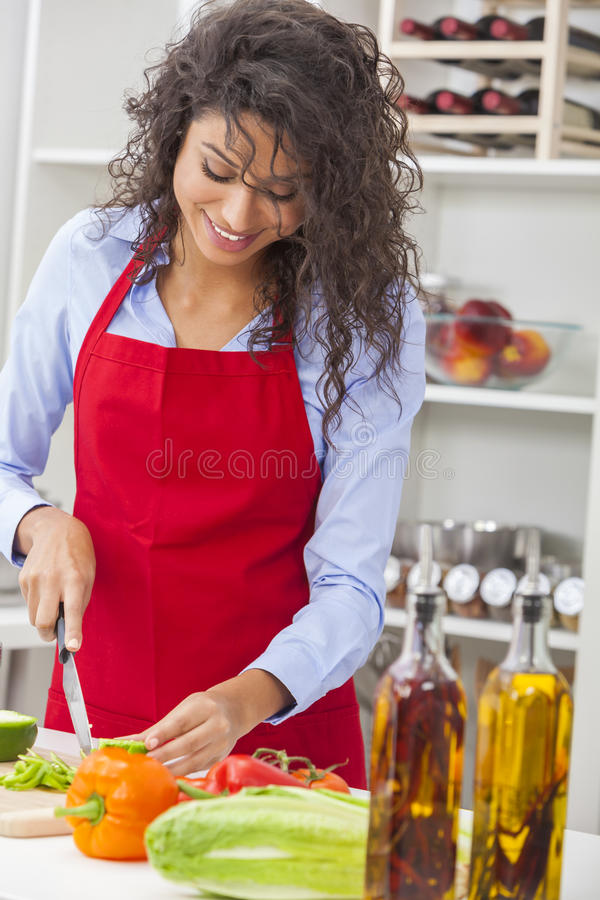Woman Preparing Vegetables Salad Food in Kitchen. A beautiful happy young woman or girl wearing glasses & a red apron cutting & preparing fresh vegetable salad royalty free stock images