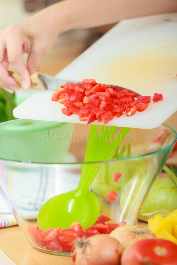 Woman preparing vegetables salad slicing red pepper. Healthy eating, vegetarian food, cooking, dieting and people concept. Woman in kitchen at home preparing royalty free stock image