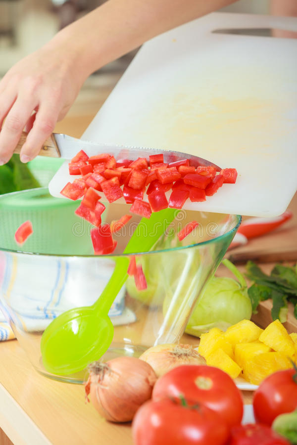 Woman preparing vegetables salad slicing red pepper. Healthy eating, vegetarian food, cooking, dieting and people concept. Woman in kitchen at home preparing stock photography