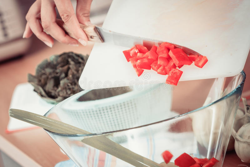 Woman preparing vegetables salad slicing red pepper. Healthy eating, vegetarian food, cooking, dieting and people concept. Woman in kitchen at home preparing stock image