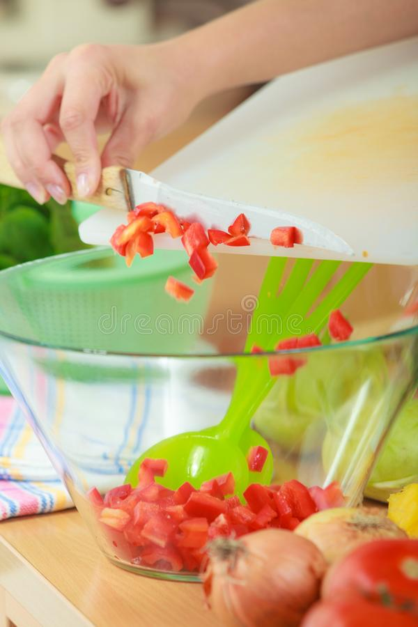 Woman preparing vegetables salad slicing red pepper. Healthy eating, vegetarian food, cooking, dieting and people concept. Woman in kitchen at home preparing royalty free stock photos
