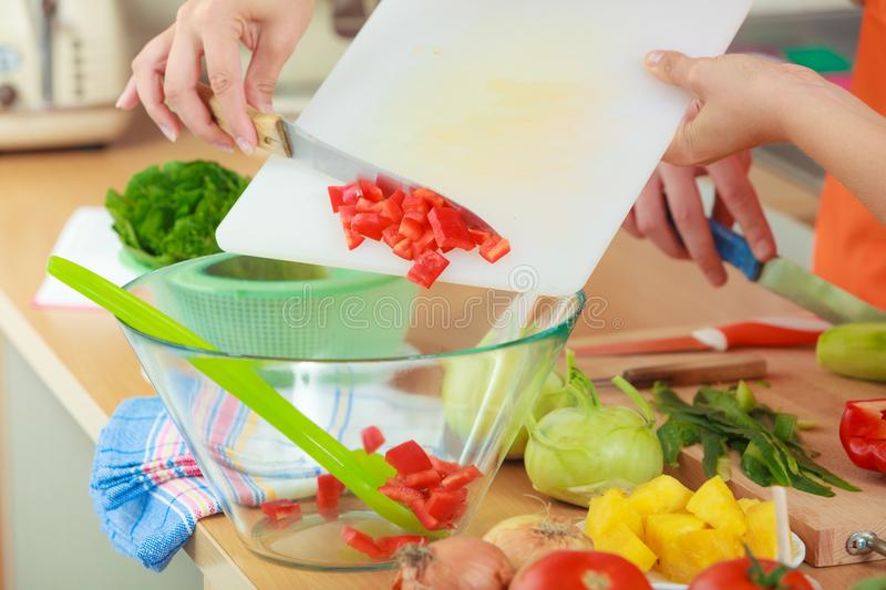 Woman preparing vegetables salad slicing red pepper. Healthy eating, vegetarian food, cooking, dieting and people concept. Woman in kitchen at home preparing stock images