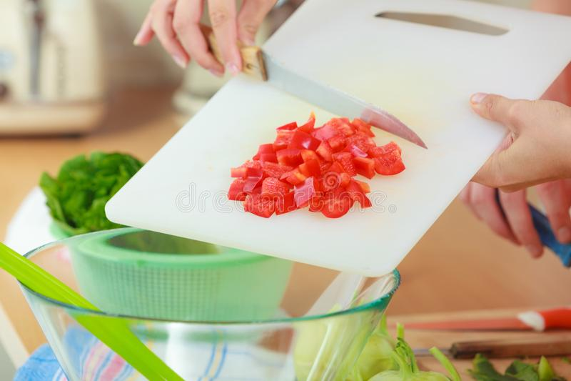 Woman preparing vegetables salad slicing red pepper. Healthy eating, vegetarian food, cooking, dieting and people concept. Woman in kitchen at home preparing stock photo