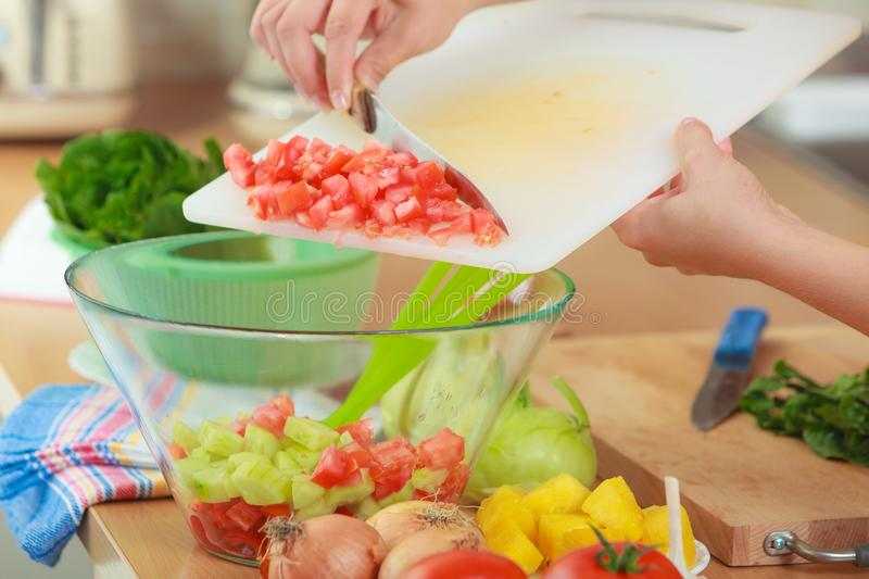 Woman preparing vegetables salad slicing tomato. Healthy eating, vegetarian food, cooking, dieting and people concept. Woman in kitchen at home preparing fresh stock photography