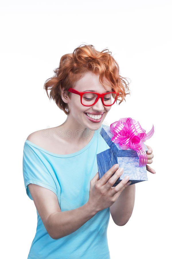 Woman with present. Beautiful young smiling girl with red hair holding a blue gift box with a bright pink bow on white background. Studio shot stock image