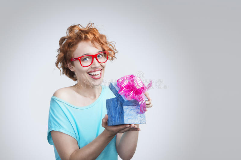 Woman with present box. Beautiful young smiling girl with red hair holding a blue gift box with a bright pink bow. Gray background. Studio shot royalty free stock photography