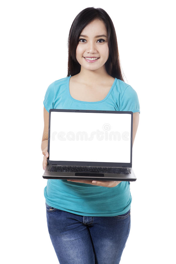 Woman presenting blank laptop screen. Beautiful woman showing a laptop on white background royalty free stock images